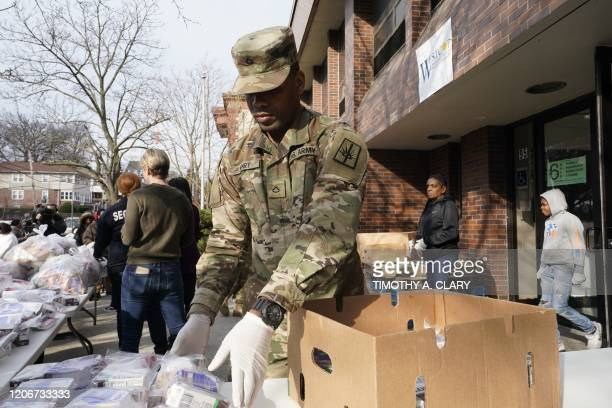 National Guard troops give food to residents of New Rochelle New York at Westchester Community Opportunity Program Inc on March 12 2020 The National...