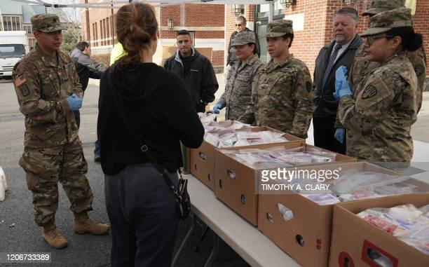 National Guard troops give food to residents of New Rochelle New York at New Rochelle High School March 12 2020 The National Guard will help clean...