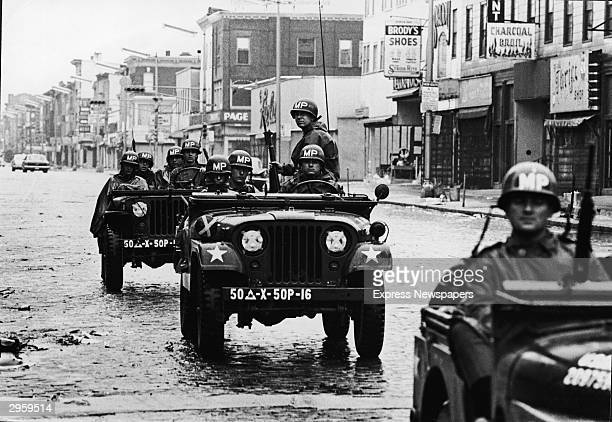 National Guard troops in jeeps patrol the empty streets of Newark during a period of rioting and civil unrest New Jersey 1967