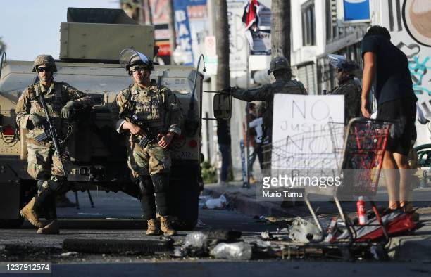 National Guard troops keep watch in the Fairfax District, an area damaged during yesterday's unrest, after the troops were activated by California...