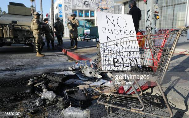 National Guard troops keep watch next to a sign reading 'No Justice No Peace' in the Fairfax District, an area damaged during yesterday's unrest,...