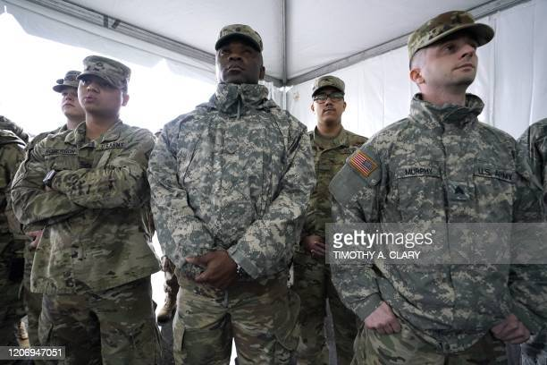 National Guard troops listen to New York Governor Andrew Cuomo as people wait to be tested at the State's First Drive Through COVID19 Mobile Testing...