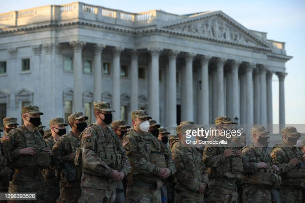 National Guard troops pose for photographers on the East Front of the U.S. Capitol the day after the House of Representatives voted to impeach...