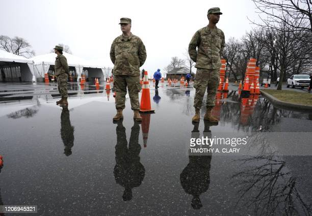 National Guard troops stand by as people wait to be tested for Coronavirus at the State's First Drive Through COVID19 Mobile Testing Center at Glen...