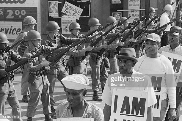 National Guard troops stand with bayonets fixed as AfricanAmerican sanitation workers peacefully march by while wearing placards reading I AM A MAN...