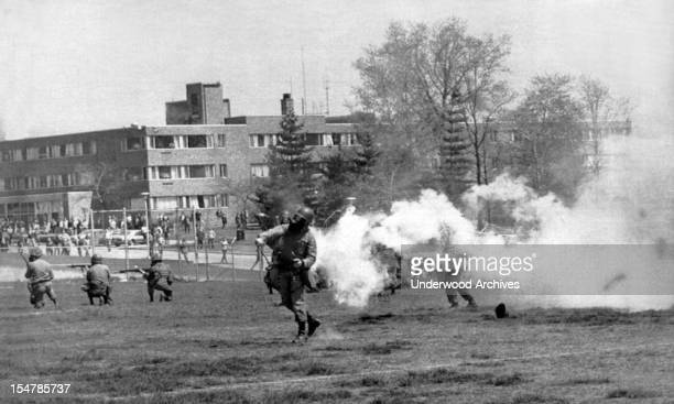 National Guard troops throw tear gas into the rioters at Kent State protesting the American invasion of Cambodia. Shortly after the troops opened...