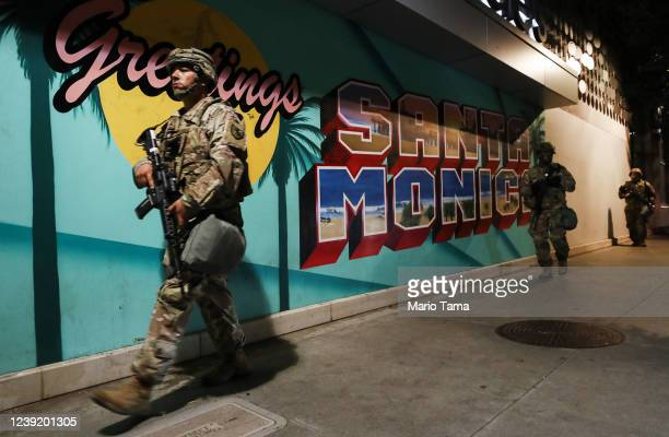 S National Guard troops walk past a 'Greetings From Santa Monica' mural outside a Bloomingdale's which was looted in the aftermath of George Floyd's...