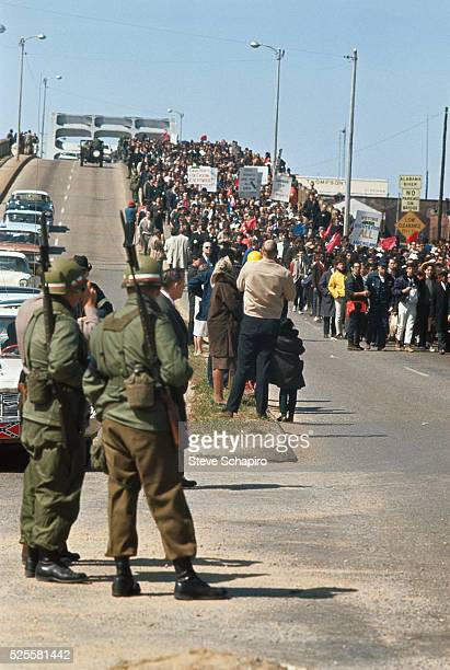 National Guard troops watch civil rights activists march from Selma over the Edmund Pettus Bridge They are on their way to Montgomery to protest...