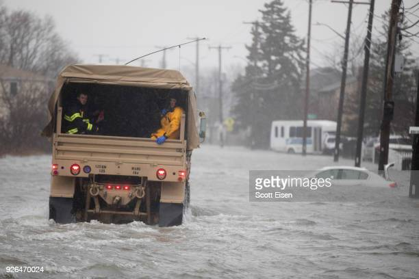 National Guard vehicle brings emergency workers to residents trapped by flood waters due to a strong coastal storm on March 2 2018 in Quincy...