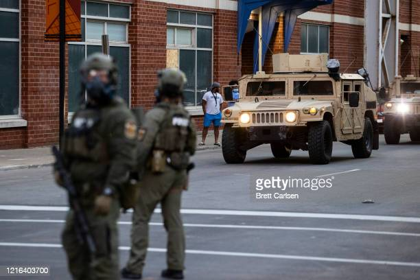 National Guard vehicles drive into downtown behind police officers in riot gear as protests occur on May 30 2020 in Louisville Kentucky Protests have...