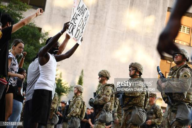 TOPSHOT National Guards form a line in front of Black Lives Matter protestors in Tulsa Oklahoma where Donald Trump holds a campaign rally at the BOK...