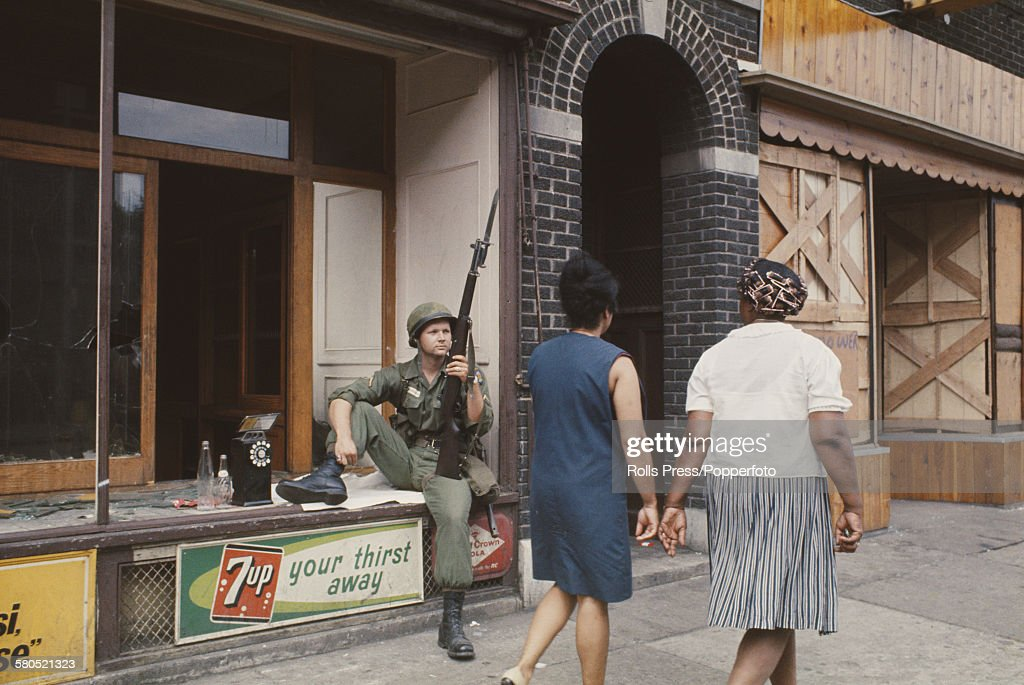 A National Guardsman armed with a rifle and bayonet rests in the window of a wrecked shop front in a shopping street in Detroit following three days and nights of rioting sparked by a police raid on an unlicensed bar in July 1967.
