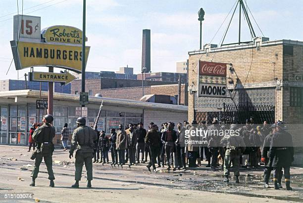 National Guardsman attempt crowd control after riots broke out in Chicago after the assassination of Martin Luther King To the right two fireman are...