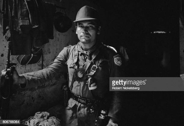 National Guardsman stands at his post in a rural town near Farabundo Martí National Liberation Front controlled territory near Jucuarán in southern...