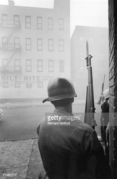 A National Guardsman stands behind a corner and holds a Garand rifle with fixed bayonet during the suppression of riots Newark New Jersey July 1967 A...