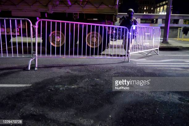 National Guardsman stands near the scared asphalt caused by a fire in a police vehicle during riots in the summer, as the National Guards is deployed...