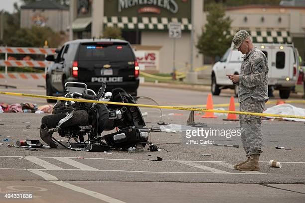 National Guardsman stands over a wrecked police motorcycle on the scene after a suspected drunk driver crashed into a crowd of spectators during the...