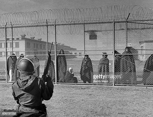 A National Guardsman watches prisoners behind a fence after a riot in the New Mexico State Prison The prisoners are draped in blankets to stave off...