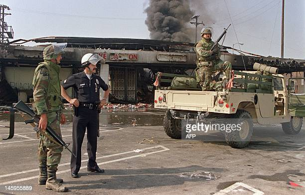 National Guardsmen and a police officer take up security positions in front of a burned and looted shopping center 01 May 1992 in central Los Angeles...