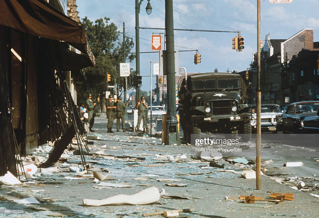 National Guardsmen armed with rifles stand guard amid debris littering the streets of the West Side of Detroit following days and nights of rioting sparked by a police raid on an unlicensed bar in July 1967.