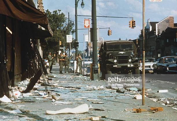 National Guardsmen armed with rifles stand guard amid debris littering the streets of the West Side of Detroit following days and nights of rioting...