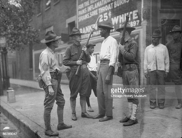 National Guardsmen called in by Mayor 'Big Bill' Thompson after three days of rioting question an African American man in Chicago 1919 The National...