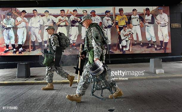 National Guardsmen carry riot gear past a mural of Pittsburgh's baseball heroes near the site of the G20 Summit on September 24 2009 in downtown...