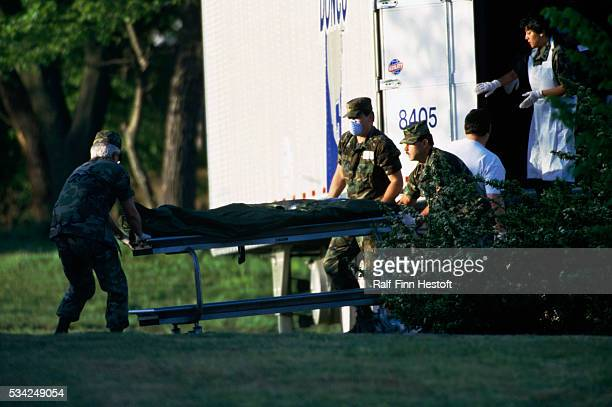 National Guardsmen ferry body bags of victims from refrigerated trucks to the state medical examiner's office in the aftermath of the Oklahoma City...
