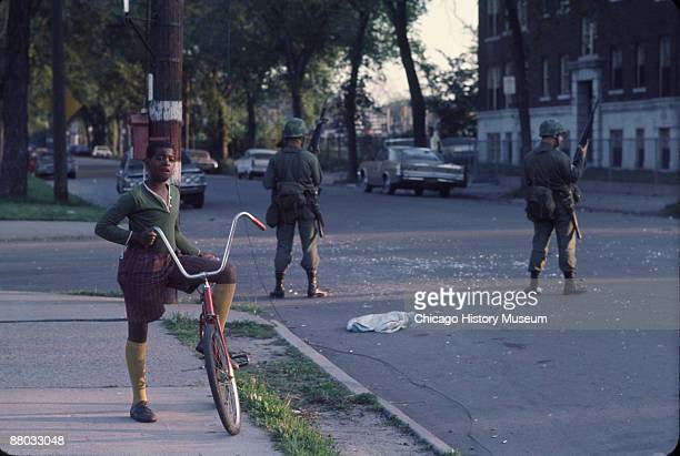 National Guardsmen stand guard as a young boy pauses from riding his bicycle in the west side neighborhood of Lawndale Chicago 1968 The guardsmen...
