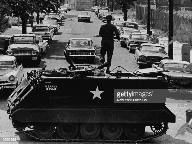 A National Guardsmen stands with a rifle atop a personnel carrier vehicle blocking traffic leaving the area during race riots Newark New Jersey July...