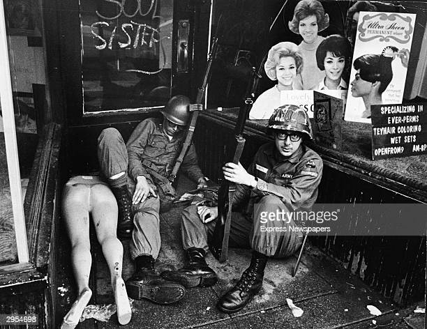National Guardsmen take a break and rest in front of a hairdressers shop during race riots which took place in Newark New Jersey July 1967
