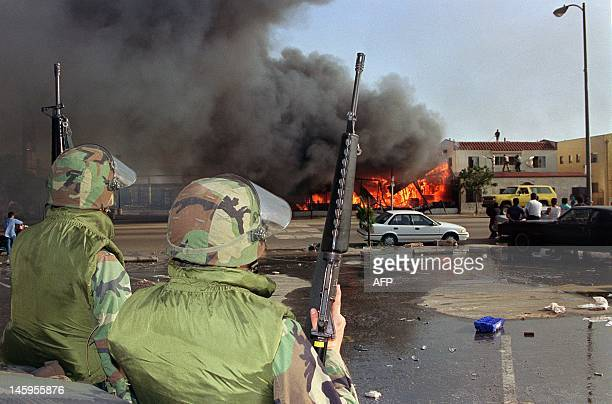 National Guardsmen watch a business go up in flames in South Los Angeles 30 April 1992 The 1992 Los Angeles riots with looting and arson events...