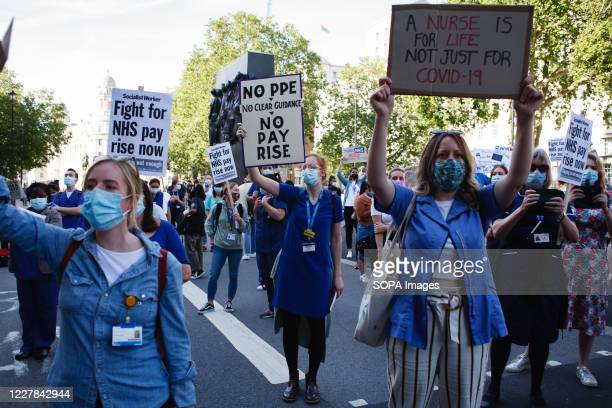 National Health Service staff are seen wearing masks while showing placards in their protest against exclusion from a recently-announced public...