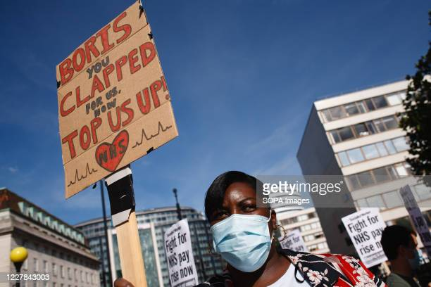 National Health Service staff wearing a mask is seen protesting their exclusion from a recently-announced public sector pay rise, demonstrate outside...