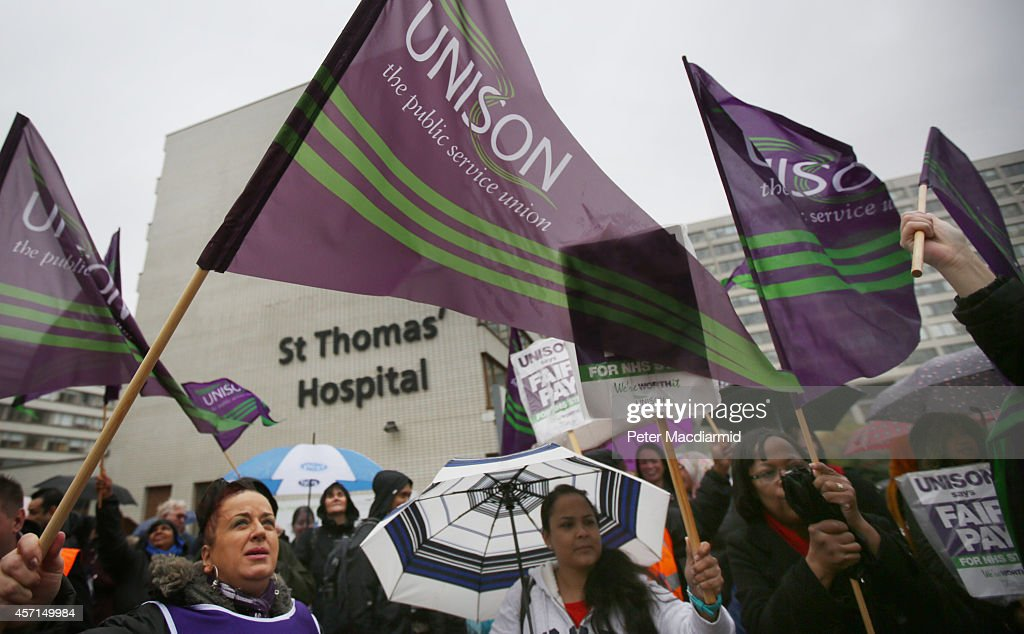 National Health Service (NHS) workers gather outside St Thomas' Hospital on October 13, 2014 in London, England. NHS workers are holding a four hour strike over pay. Unions are seeking a 1% rise for all workers, but the government are saying that it would cost too much.