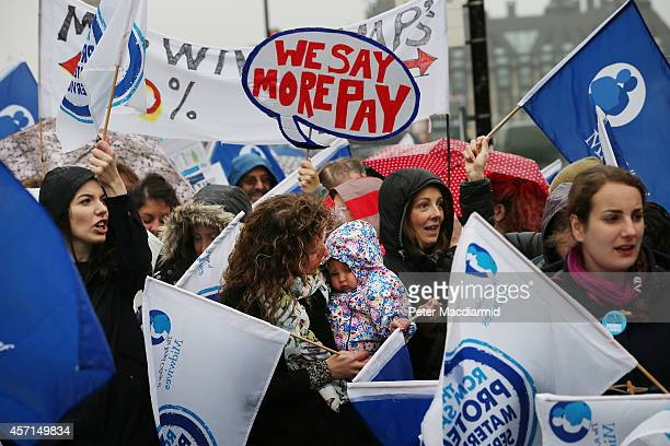 National Health Service workers including a midwife and her baby gather outside St Thomas' Hospital on October 13 2014 in London England NHS workers...