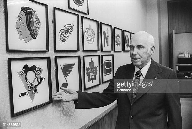 National Hockey League President Clarence Campbell looks over some of the team crests in his office