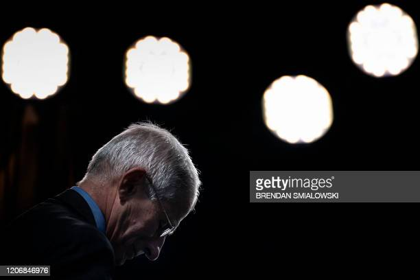 National Institute of Allergy and Infectious Diseases Director Dr Anthony Fauci pauses after during a TV interview outside the White House March 12...