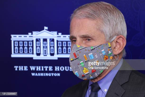 National Institute of Allergy and Infectious Diseases Director Dr. Anthony Fauci wears a lab-themed face mask while talking to reporters in the Brady...