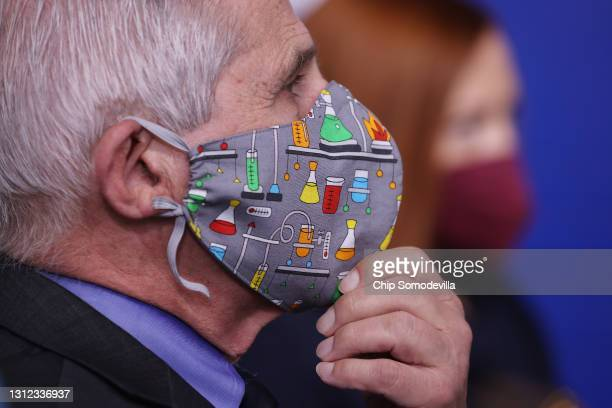 National Institute of Allergy and Infectious Diseases Director Dr. Anthony Fauci adjust his lab-themed face mask while talking to reporters in the...