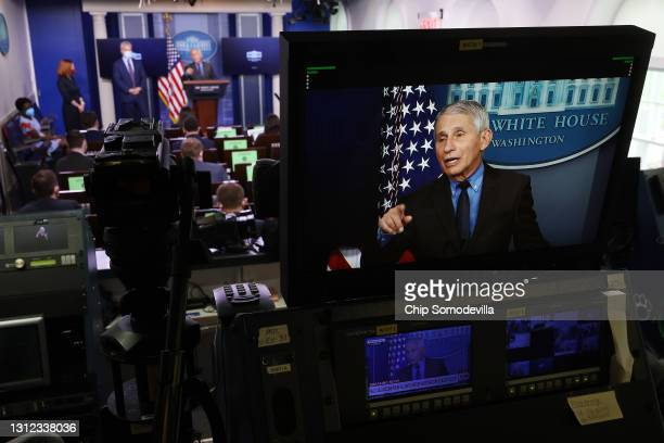 National Institute of Allergy and Infectious Diseases Director Dr. Anthony Fauci appears on a television screen while talking to reporters in the...