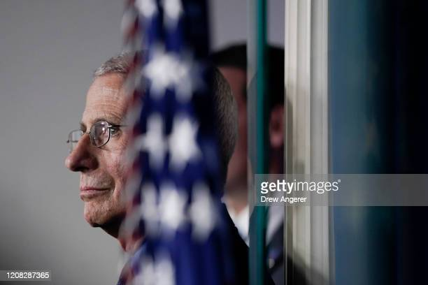 National Institute of Allergy and Infectious Diseases Director Anthony Fauci listens as U.S. President Donald Trump speaks during a briefing on the...