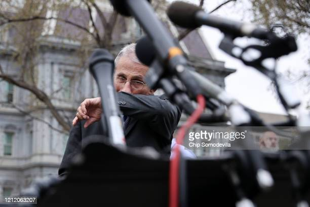 National Institute Of Allergy And Infectious Diseases Director Anthony Fauci wipes his face before talking to reporters about the Trump...