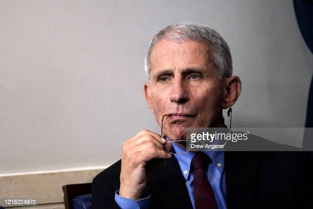 National Institute of Allergy and Infectious Diseases Director Anthony Fauci listens during a briefing on the coronavirus pandemic in the press...