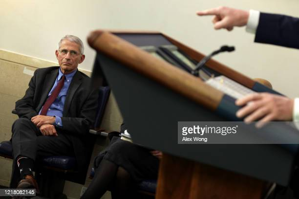 National Institute of Allergy and Infectious Diseases Director Anthony Fauci watches as U.S. President Donald Trump makes a point during the daily...