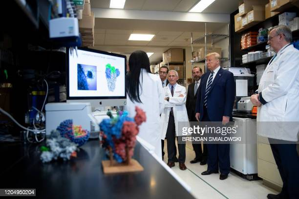 National Institute of Allergy and Infectious Diseases Director Tony Fauci looks on next to US President Donald Trump during a tour of the National...