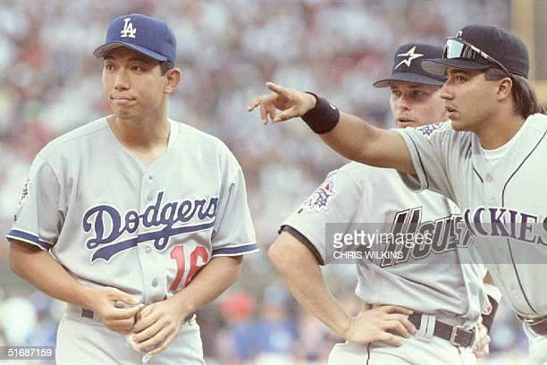 National League All-Star teammates Vinny Castilla of the Colorado Rockies and Craig Biggio of the Houston Astros point starting pitcher Hideo Nomo...
