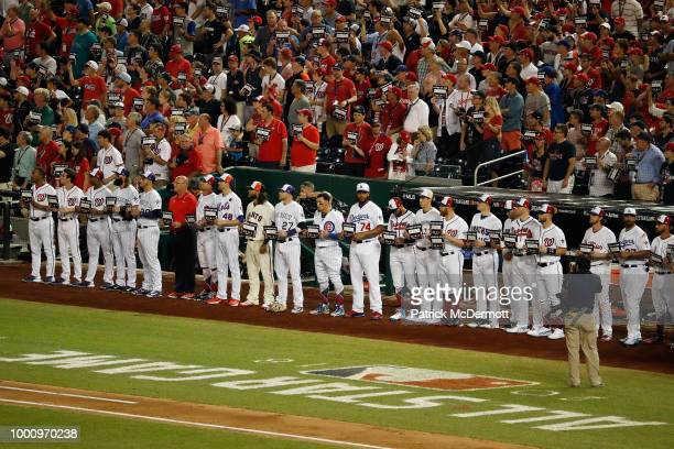 National League AllStars and fans hold up Stand Up To Cancer signs during the 89th MLB AllStar Game presented by Mastercard at Nationals Park on July...
