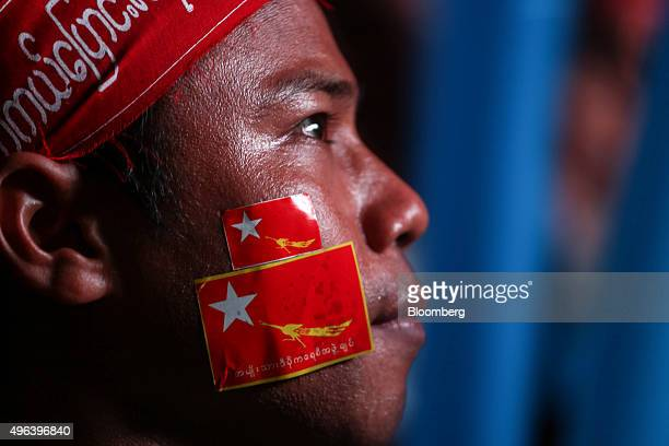 A National League for Democracy party supporter with party flags on his cheeks looks on during celebrations following the nation's historic election...
