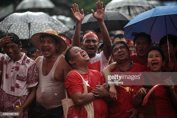 National League for Democracy party supporters celebrate election results under heavy rain outside the party headquarters in Yangon Myanmar on Monday...